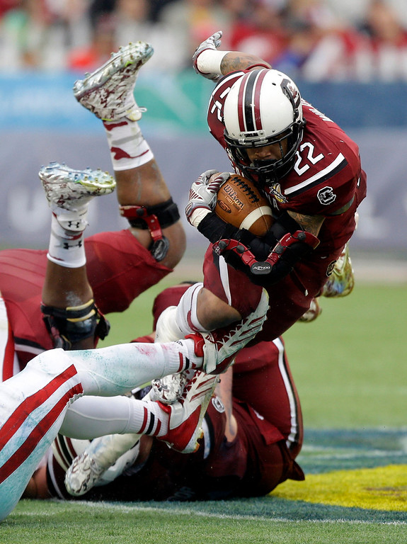 . South Carolina running back Brandon Wilds (22) dives for a short gain as he is tripped up by the Wisconsin defense during the first half of the Capital One Bowl NCAA college football game in Orlando, Fla., Wednesday, Jan. 1, 2014.(AP Photo/John Raoux)