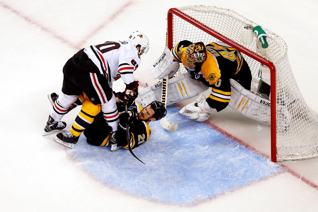 . Brandon Saad #20 of the Chicago Blackhawks collides with Andrew Ference #21 of the Boston Bruins in front of Tuukka Rask #40 in Game Four of the 2013 NHL Stanley Cup Final at TD Garden on June 19, 2013 in Boston, Massachusetts.  (Photo by Jim Rogash/Getty Images)