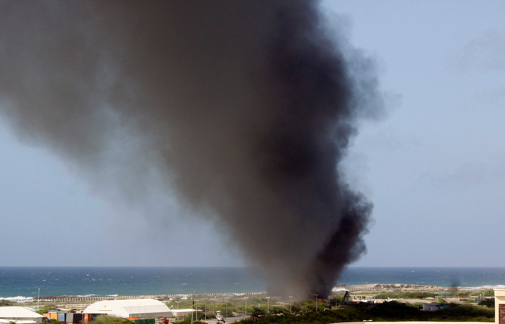 . Black smoke rises over the scene of a plane crash at the Mogadishu airport  Friday, Aug. 9, 2013.  (AP Photo/Farah Abdi Warsameh)