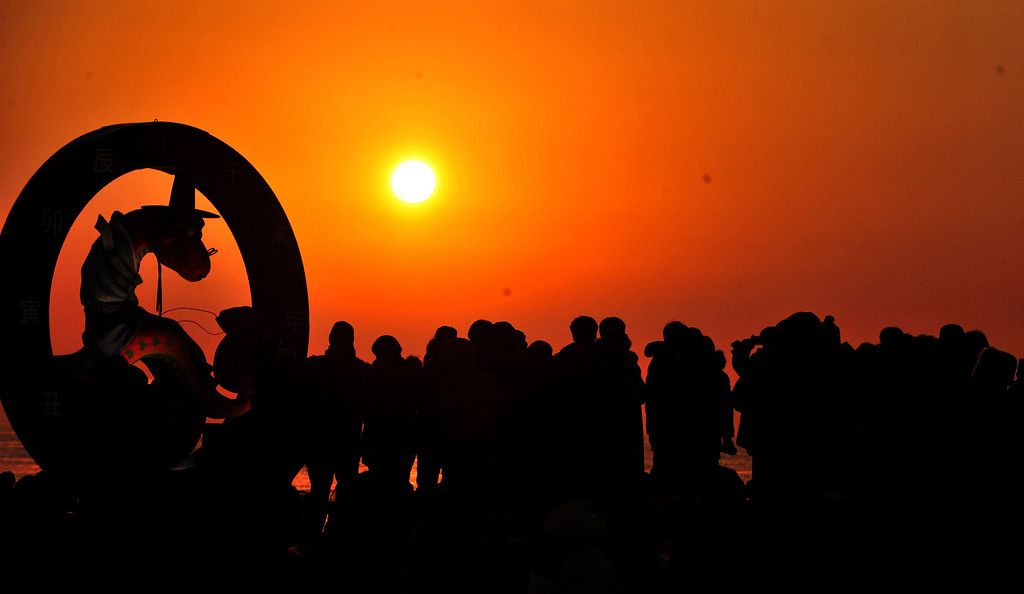 . People watch sunrise on the beach as they greet the new year in Ulsan, southeast of Seoul January 1, 2013.    REUTERS/Lee Sang-hyun/Yonhap