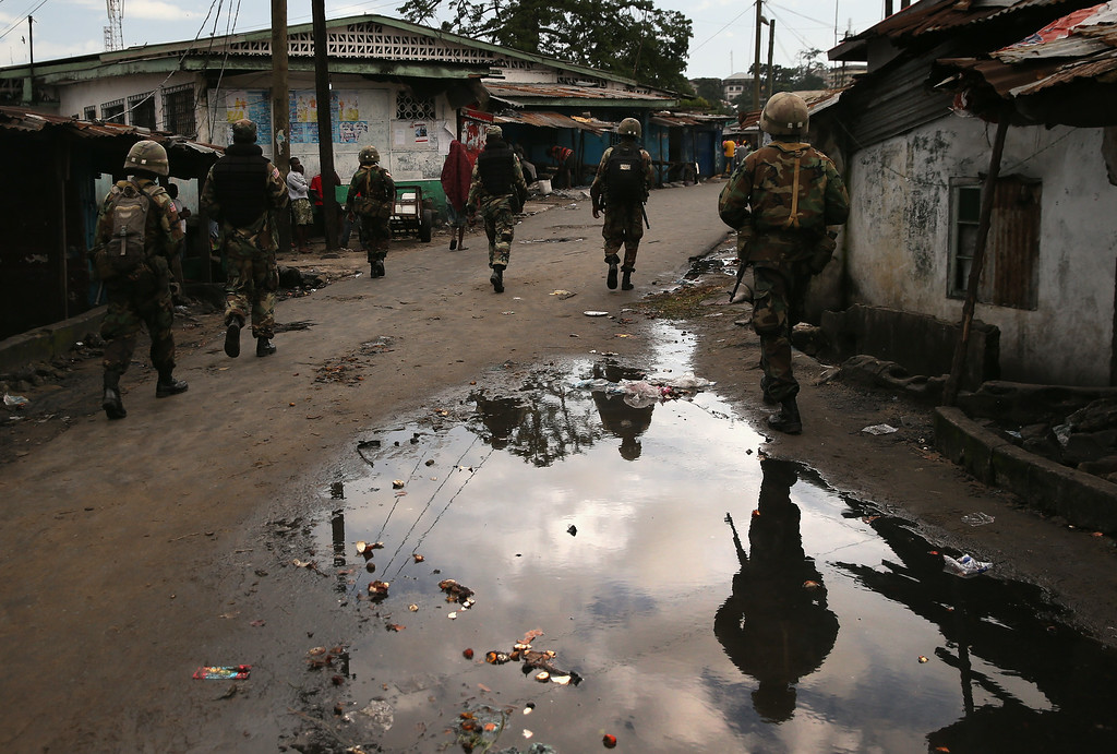 . MONROVIA, LIBERIA - AUGUST 20:  Liberian security forces, part of the country\'s Ebola Task Force, enforce a quarantine on the West Point slum on August 20, 2014 in Monrovia, Liberia. The quarantine of West Point, a congested favella of 75,000 people, began Wednesday, as the government tries to stop the spread of the virus in the capital city. A mob overran and closed an Ebola isolation ward there on August 16. The Ebola virus has killed more than 1,200 people in four African nations, more in Liberia than any other country.  (Photo by John Moore/Getty Images)