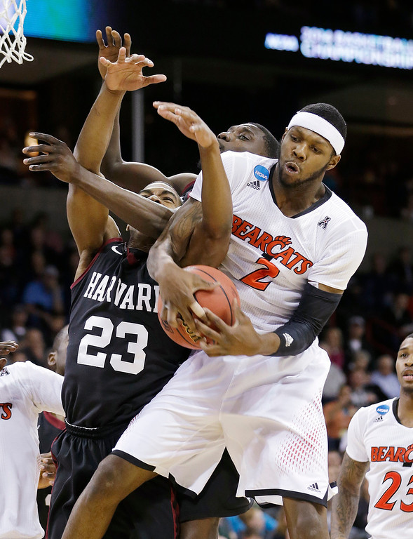 . Cincinnati\'s Titus Rubles, right, gets tangled-up with Harvard\'s Wesley Saunders (23) and Kyle Casey in the second half of a second-round game of the NCAA college basketball tournament in Spokane, Wash., Thursday, March 20, 2014. (AP Photo/Elaine Thompson)