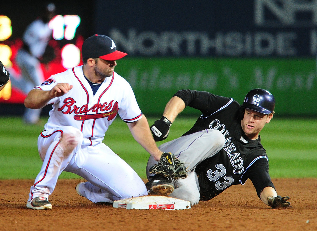 . ATLANTA, GA - MAY 23: Justin Morneau #33 of the Colorado Rockies slides in to second base for an 8th inning double against Dan Uggla #26 of the Atlanta Braves at Turner Field on May 23, 2014 in Atlanta, Georgia. (Photo by Scott Cunningham/Getty Images)