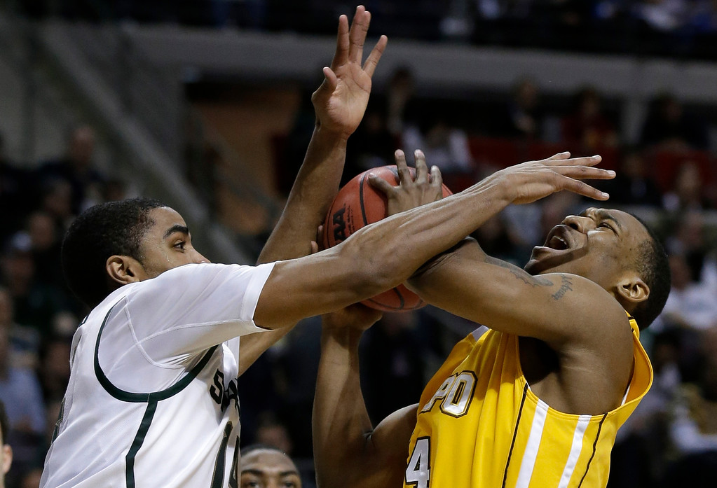 . Michigan State guard Gary Harris (14), left,  defends Valparaiso guard LaVonte Dority (4) in the first half of a second-round game of the NCAA college basketball tournament in Auburn Hills, Mich., Thursday March 21, 2013. (AP Photo/Paul Sancya)