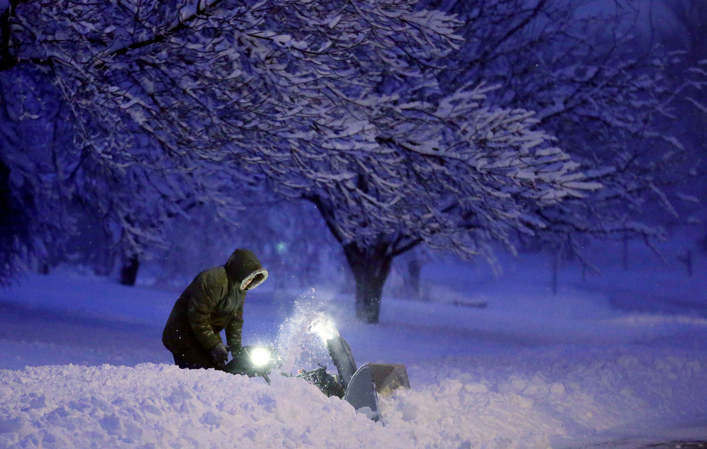 . A local resident clears snow from his driveway after an overnight snowfall left many schools and businesses closed for the day, Thursday, Dec. 20, 2012, in Urbandale, Iowa. (AP Photo/Charlie Neibergall)