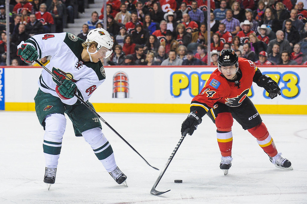 . Jiri Hudler #24 of the Calgary Flames fights for the puck against Mikael Granlund #64 of the Minnesota Wild during an NHL game at Scotiabank Saddledome on February 1, 2014 in Calgary, Alberta, Canada. (Photo by Derek Leung/Getty Images)