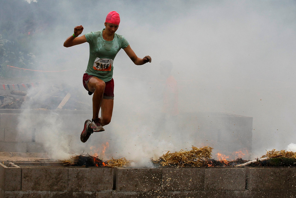 """. A female participant of the \""""Tough Mudder\"""" endurance event series jumps over an open fire of the \""""Fire Walker\"""" obstacle in the Fursten Forest, a former British Army training ground near the north-western German city of Osnabrueck July 13, 2013. The hardcore but un-timed event over 16 km (10 miles) was designed by British Special Forces to test mental as well as physical strength. Some 4,000 competitors had to overcome obstacles of common human fears, such as fire, water, electricity and heights.   REUTERS/Wolfgang Rattay"""