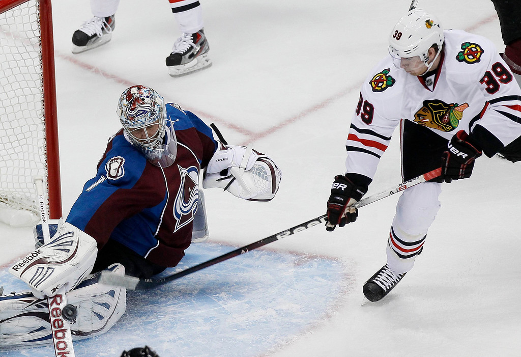 . Chicago Blackhawks\' Jimmy Hayes (R) slips the puck past the stick of Colorado Avalanche goalie Semyon Varlamov to score a first period goal in their NHL hockey game in Denver March 18, 2013. REUTERS/Rick Wilking