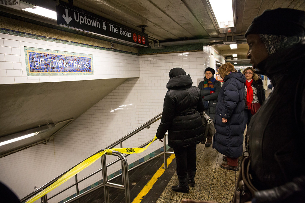 . People stand outside the blocked entrance to the 1-2-3 train at the Times Square subway station on February 5, 2014 in New York, United States. Due to a power failure earlier in the morning, the 1-2-3 train experienced extensive delays, eventually causing the Metropolitan Transportation Authority to shut the train line down for a period, lengthening commutes for many New Yorkers.  (Photo by Andrew Burton/Getty Images)