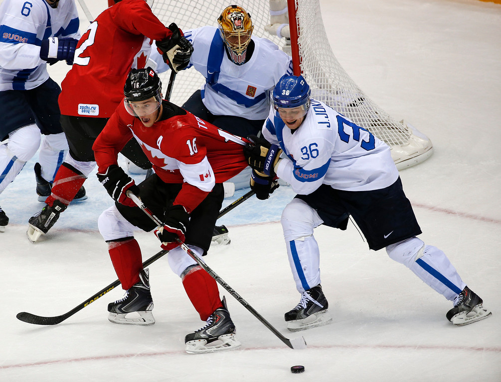 . Finland forward Jussi Jokinen grabs Canada forward Jonathan Toews\' jersey in the third period of a men\'s ice hockey game at the 2014 Winter Olympics, Sunday, Feb. 16, 2014, in Sochi, Russia. (AP Photo/Julio Cortez)