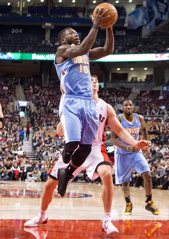 . Denver Nuggets\' Nate Robinson, left, goes up for a basket as Toronto Raptors\' Tyler Hansbrough look on during the second half of an NBA basketball game on Sunday, Dec. 1, 2013, in Toronto. (AP Photo/The Canadian Press, Chris Young)
