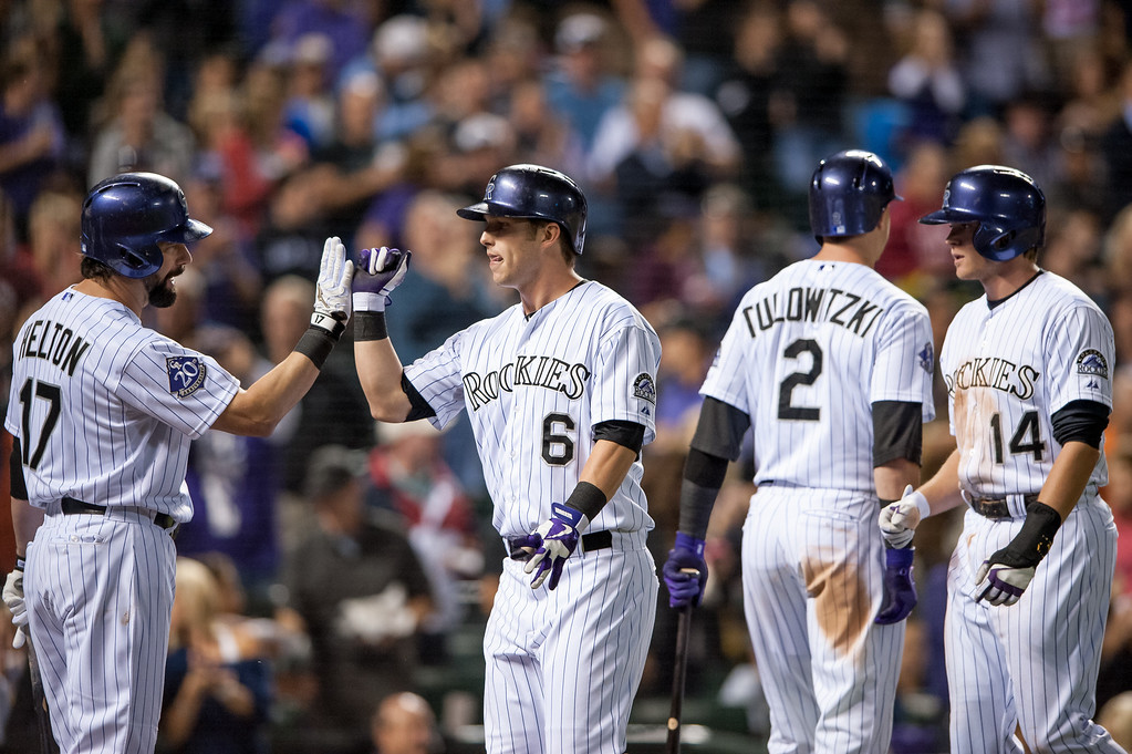 . DENVER, CO - SEPTEMBER 20:  Corey Dickerson #6 of the Colorado Rockies is congratulated by teammate Todd Helton #17 as Troy Tulowitzki #2 and Josh Rutledge #14 of the Rockies also celebrate a sixth-inning two-run home run hit by Dickerson against the Arizona Diamondbacks at Coors Field on September 20, 2013 in Denver, Colorado. (Photo by Dustin Bradford/Getty Images)