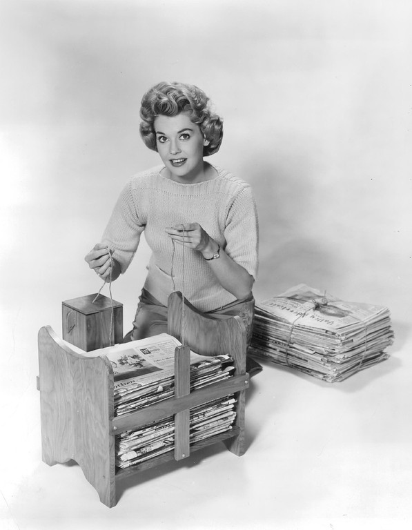 . Newspaper bundler shown here with TV actress Donna Douglas makes storage easy and orderly. It holds a month\'s accumulation and everything that you need to tie the papers in neat bundles is built in. March 1962. (From The Denver Post Library Archive)