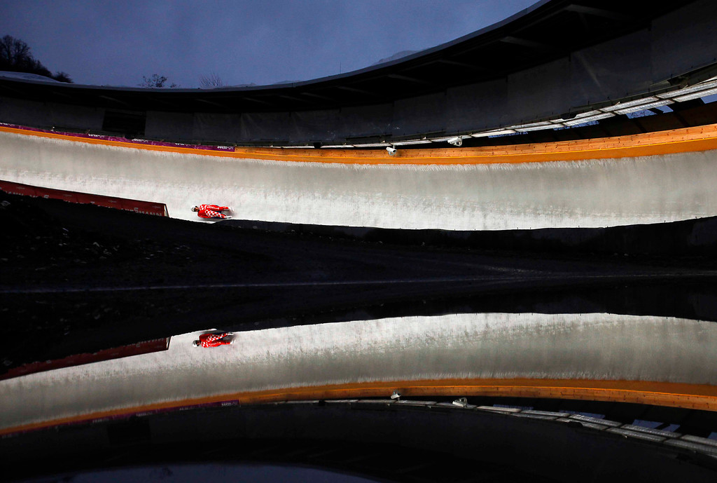 . An Austrian athlete is reflected in a puddle of rain, competes in the men\'s training race at the Sliding Center Sanki during the the Luge World Cup 2013, in Krasnaya Polyana resort, some 60 kilometers (37 miles) east of Sochi, Russia, Friday, Feb. 22, 2013. (AP Photo/Alexander Zemlianichenko, FIle)