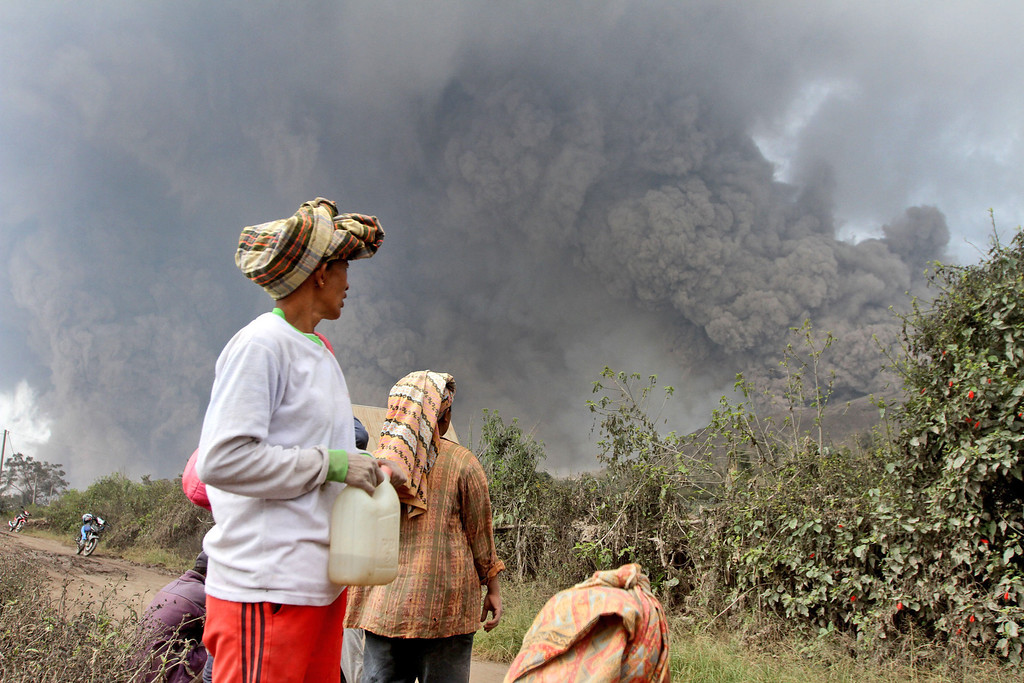 . Villagers watch as Mount Sinabung releases pyroclastic flows during an eruption in Namantaran, North Sumatra, Indonesia, Saturday, Feb. 1, 2014. The rumbling volcano in western Indonesia has unleashed fresh clouds of searing gas, killing a number people and injuring few others. (AP Photo)