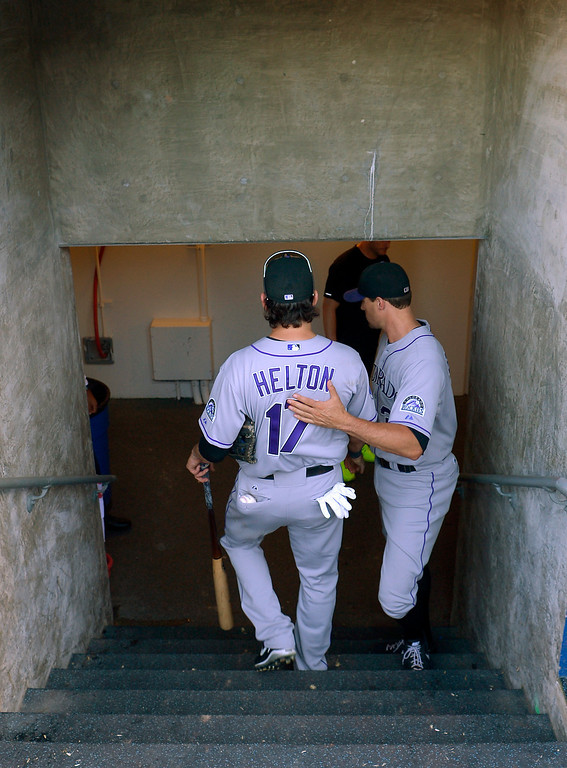 . Colorado Rockies\' Todd Helton, left, gets a pat on the back from Matt Belisle as he leaves the field after the Rockies defeated the Los Angeles Dodgers 2-1 in a baseball game, Sunday, Sept. 29, 2013, in Los Angeles. Helton was playing in the final game of his career. (AP Photo/Mark J. Terrill)