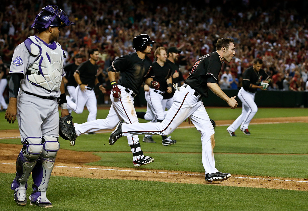 . Arizona Diamondbacks\' A.J. Pollock, front right, who scored the game-winning run, joins other teammates as they run out to teammate Cody Ross, who hits the sacrifice fly to knock Pollock in, as Colorado Rockies\' Wilin Rosario, left, looks on in the 10th inning during a baseball game, on Saturday, April 27, 2013, in Phoenix.  The Diamondbacks defeated the Rockies 3-2. (AP Photo/Ross D. Franklin)