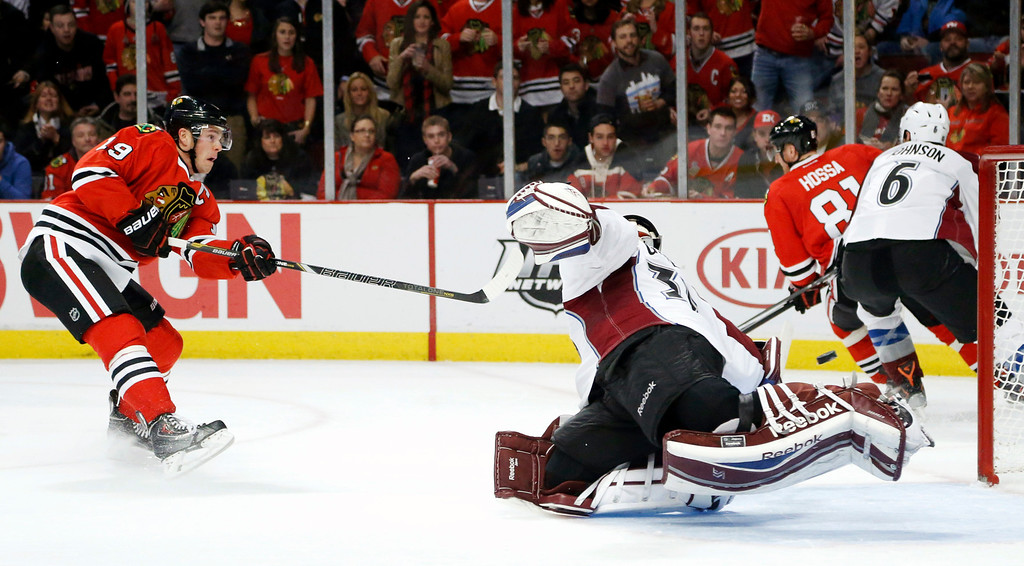 . Chicago Blackhawks center Jonathan Toews (19) shoots and scores past Colorado Avalanche goalie Jean-Sebastien Giguere during the second period of an NHL hockey game Friday, Dec. 27, 2013, in Chicago. (AP Photo/Charles Rex Arbogast)