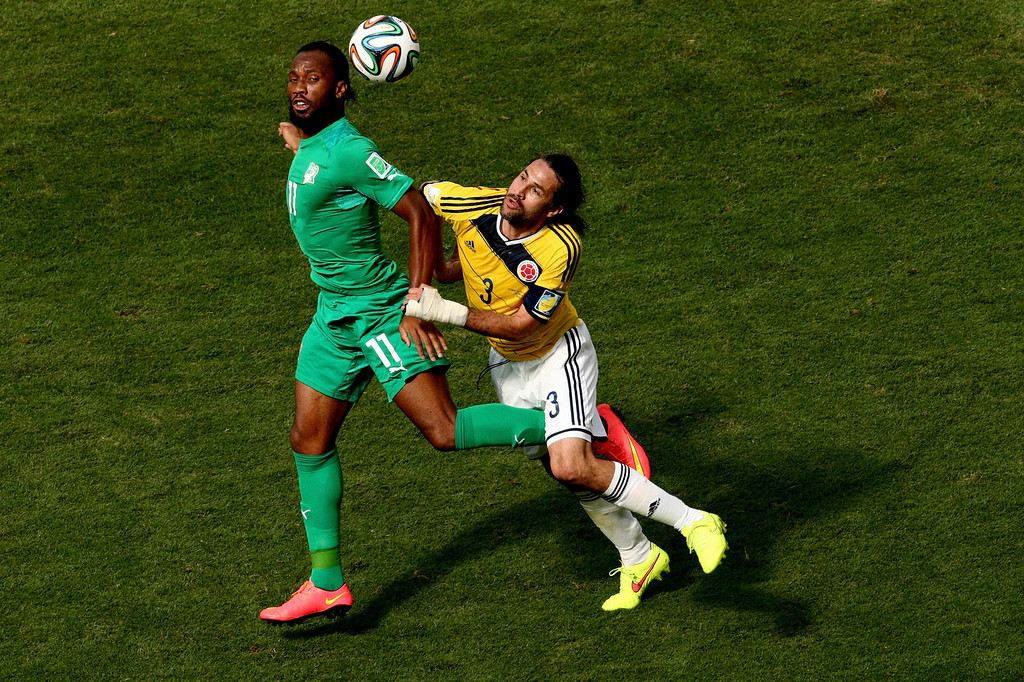 . Didier Drogba of the Ivory Coast and Mario Yepes of Colombia go up for a header during the 2014 FIFA World Cup Brazil Group C match between Colombia and Cote D\'Ivoire at Estadio Nacional on June 19, 2014 in Brasilia, Brazil.  (Photo by Adam Pretty/Getty Images)