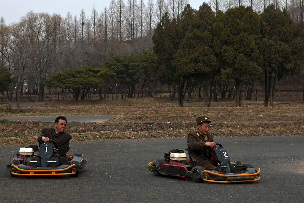 . A North Korean soldier, right, races another man on a go cart track at the Fun Fair in Pyongyang on Tuesday, April 16, 2013. (AP Photo/David Guttenfelder)