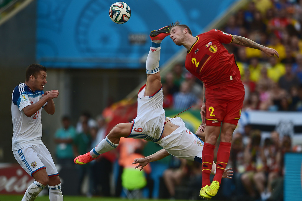 . Russia\'s forward Alexander Kokorin (C) is watched by teammate Russia\'s midfielder Viktor Faizulin (L) as he attempts to kick the ball away from Belgium\'s defender Toby Alderweireld (R) during the Group H football match between Belgium and Russia at The Maracana Stadium in Rio de Janeiro on June 22, 2014, during the 2014 FIFA World Cup. AFP PHOTO / GABRIEL BOUYS