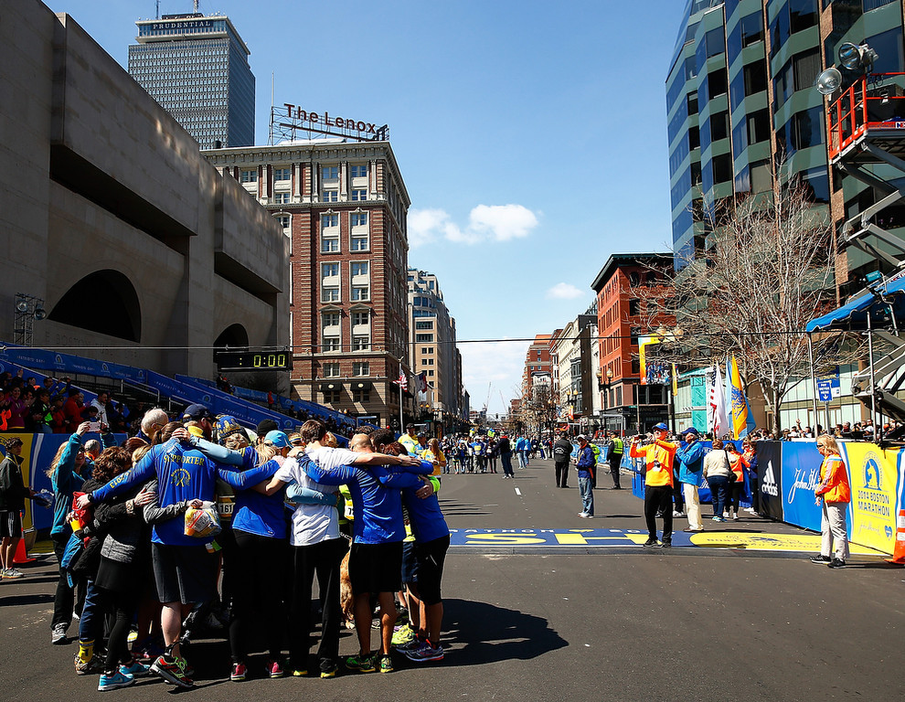 . A group huddles together after crossing the Boston Marathon finish line during the B.A.A. Tribute Run on April 19, 2014 in Boston, Massachusetts.  (Photo by Jared Wickerham/Getty Images)