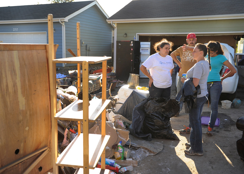. Fatima Payan, left, talked with neighbors about what assistance might be available to residents whose homes were flooded. Residents of Evans continued the grim work of salvaging personal belongings from flooded homes Saturday afternoon, September 21, 2013.  Photo By Karl Gehring/The Denver Post