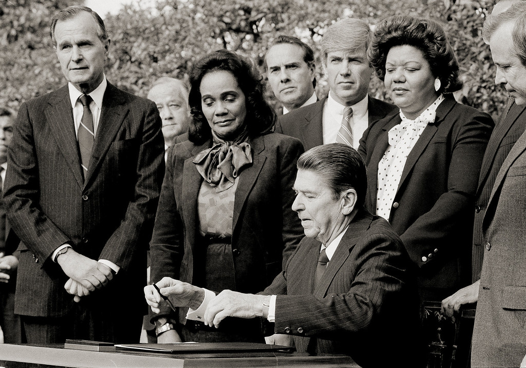 . President Ronald Reagan signs the bill making Martin Luther King, Jr.\'s birthday into a national holiday, as Coretta Scott King watches, Nov. 2, 1983, in Washington. From left are Vice President George Bush; Sen. Charles McCurdy Mathias (R-Md.); Mrs. King; Sen. Bob Dole (R-Kan.); Rep. Jack Kemp (R-N.Y.); Pres. Reagan; and Rep. Katie Hall (D-Ind.). (AP Photo/Barry Thumma)