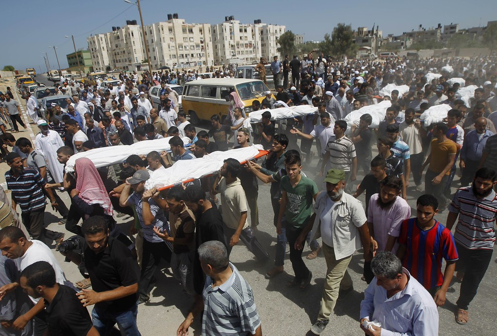 """. Palestinian mourners carry the bodies of the ten members of the al-Astal family, that were killed in an Israeli air strike on their homes, during their funeral in Khan Yunis in the southern Gaza Strip on July 30, 2014. Israeli bombardments early on July 30 killed \""""dozens\"""" Palestinians in Gaza, including at least 16 at a UN school, medics said, on day 23 of the Israel-Hamas conflict. AFP PHOTO/ SAID KHATIB/AFP/Getty Images"""