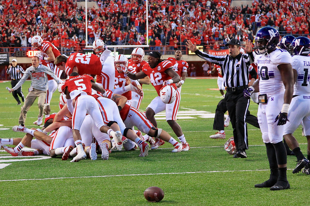 . Northwestern safety Traveon Henry (10) and others watch Nebraska players pile up following a touchdown to win in the closing seconds of an NCAA college football game in Lincoln, Neb., Saturday, Nov. 2, 2013. Nebraska won 27-24. (AP Photo/Nati Harnik)
