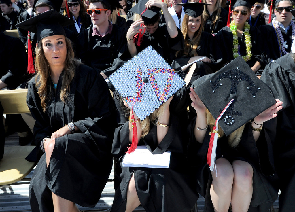 . Journalism graduates, Jenna Klein, left, Samantha Tyson and Rebecca Irwin, have impressive caps for  the 2013 University of Colorado  Spring Commencement on Friday in Folsom Field. (Cliff Grassmick/Daily Camera)