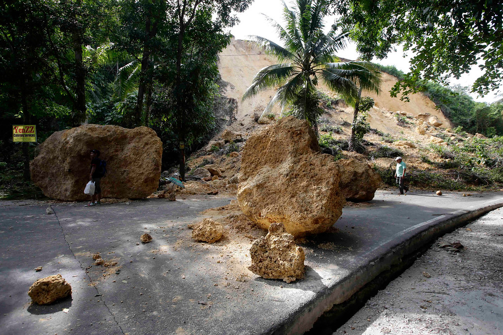 . Huge boulders block a highway at Cortes township, Bohol province in central Philippines Wednesday Oct. 16, 2013, a day after a 7.2-magnitude quake hit Bohol and Cebu provinces. . (AP Photo/Bullit Marquez)