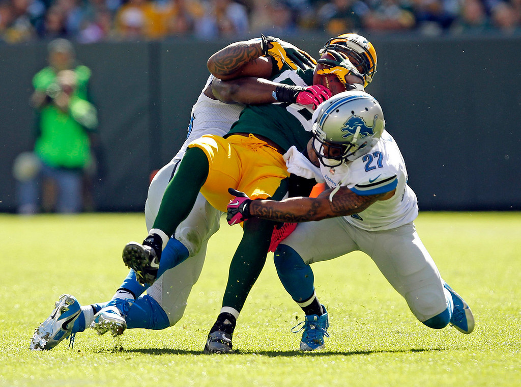 . Green Bay Packers\' Jermichael Finley is tackled by Detroit Lions\' Stephen Tulloch and Glover Quin (27) after a catch during the second half of an NFL football game Sunday, Oct. 6, 2013, in Green Bay, Wis. (AP Photo/Mike Roemer)