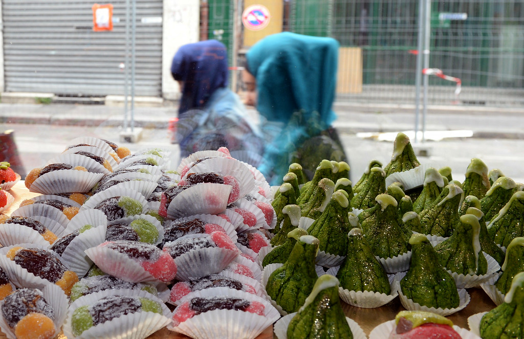". Veiled women walk past oriental pastries on display in the storefront window the ""Le Coeur d\'Alger\"" (\'Heart of Algiers\') bakery  in Bordeaux, southwestern France, on June 28, 2014, ahead of the start of Ramadan on June 29. Ramadan, the Muslim holy month of fasting, will begin on Sunday in France as well as in Saudi Arabia and many Arab countries. MEHDI FEDOUACH/AFP/Getty Images"