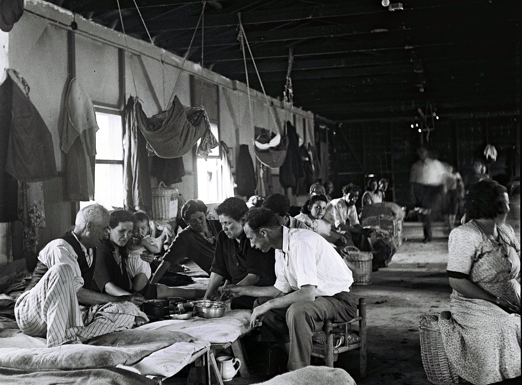 . HAIFA, ISRAEL - JULY 1, 1949: New Jewish immigrants eat their meal together in a large barracks housing entire families at the Shaar Aliya immigrants\' camp July 1, 1949 in Haifa in the newly-established State of Israel. (Photo by Zoltan Kluger/GPO via Getty Images)