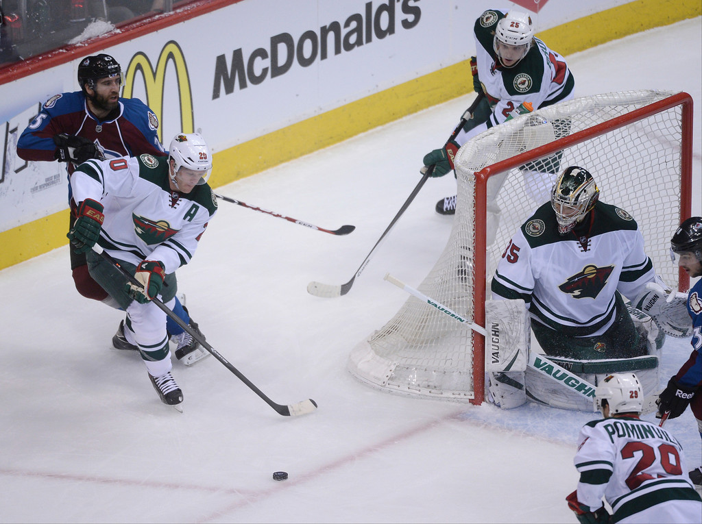 . Ryan Suter (20) takes a pass from Jonas Brodin (25) of the Minnesota Wild in front of Maxime Talbot (25) of the Colorado Avalanche during the first period of action.   (Photo by Karl Gehring/The Denver Post)