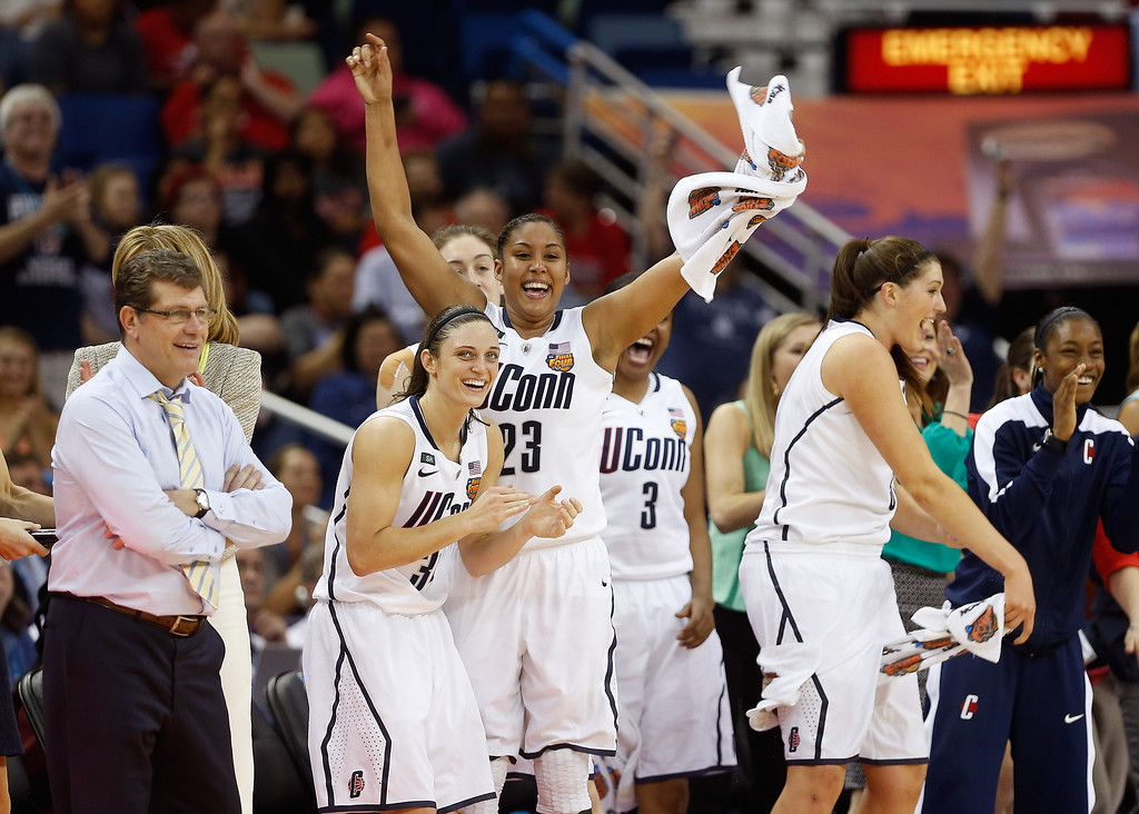 . Kelly Faris #34, Kaleena Mosqueda-Lewis #23 and head coach Geno Auriemma of the Connecticut Huskies celebrate on the bench late in the game against the Louisville Cardinals during the 2013 NCAA Women\'s Final Four Championship at New Orleans Arena on April 9, 2013 in New Orleans, Louisiana.  (Photo by Chris Graythen/Getty Images)