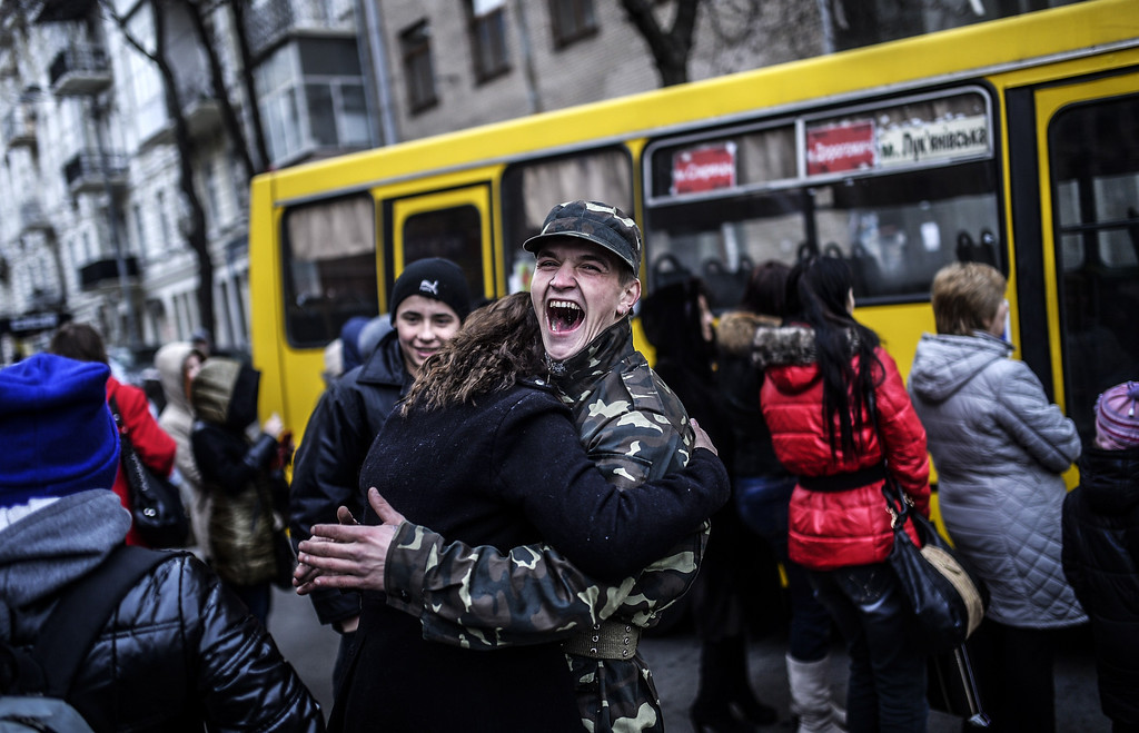 . A young couple shares a light moment while waiting at a bus stop in central Kiev on February 28, 2014. Deposed Ukrainian president Viktor Yanukovych, giving a news conference  in the southern Russian city of Rostov-on-Don, insisted on February 28, 2014 in his first public appearance since fleeing to Russia that he had not been overthrown and would continue to fight for the future of Ukraine. AFP PHOTO/BULENT  KILIC/AFP/Getty Images