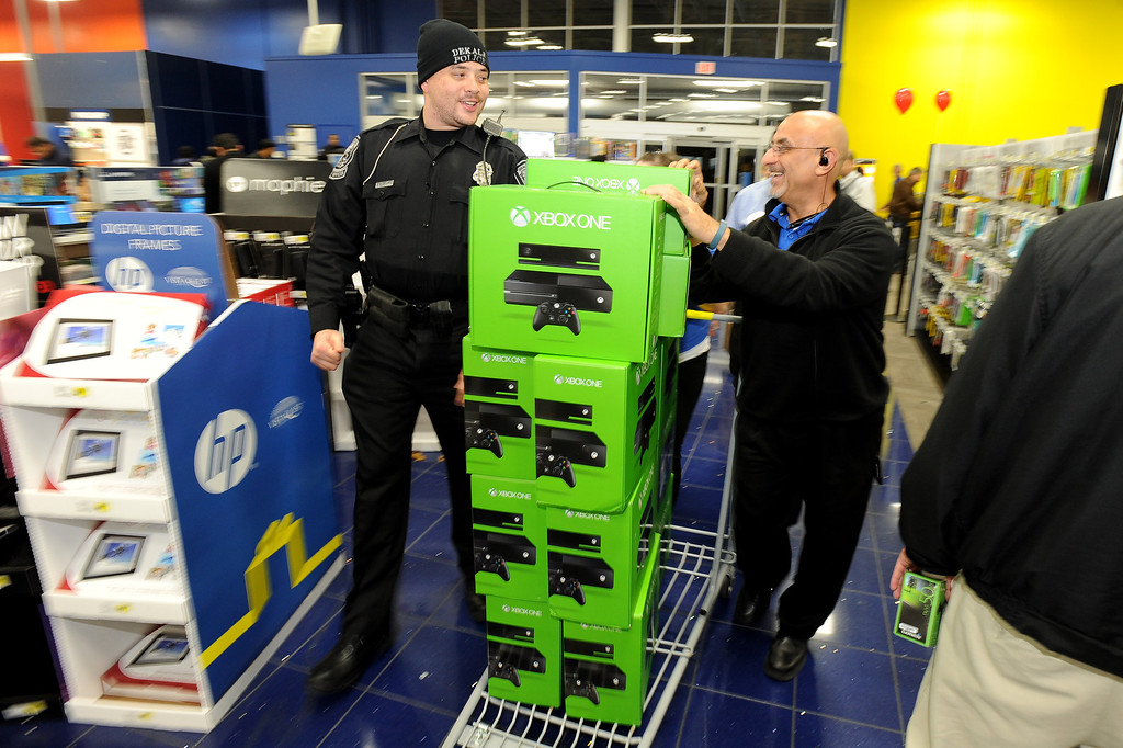 . DeKalb police Officer Q.S. Starnes, left, helps Best Buy manager Sammy Abuata wheel in a pallet of Xbox One game sets for a door-buster sale just before midnight on Thanksgiving Day, Thursday, Nov. 28, 2013, in Dunwoody, Ga. All of the store\'s 120 employees were on hand to ring up items after the electronics retailer opened on Thanksgiving this year. (AP Photo/David Tulis)