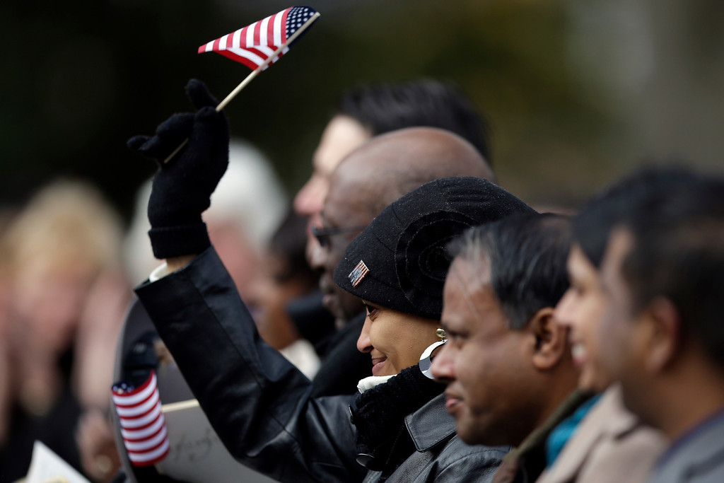 . A new citizen waves a flag after Supreme Court Justice Antonin Scalia administered the oath of allegiance, during a ceremony commemorating the 150th anniversary of the dedication of the Soldiers\' National Cemetery and President Abraham Lincoln\'s Gettysburg Address, Tuesday, Nov. 19, 2013, in Gettysburg, Pa.   (AP Photo/Matt Rourke)