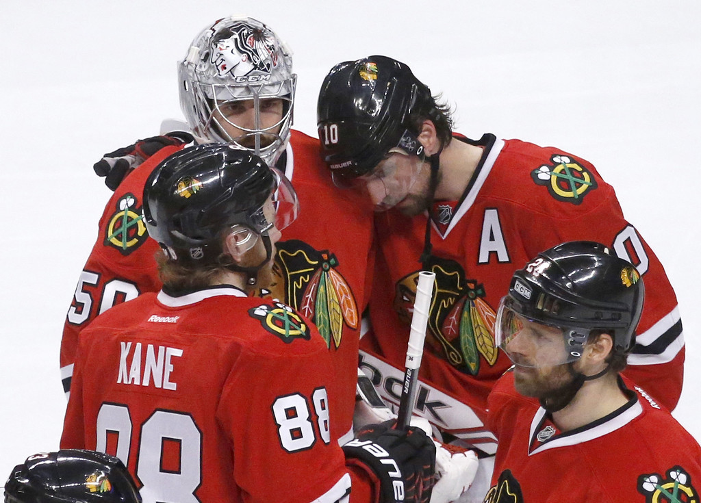 . Chicago Blackhawks\' Patrick Kane (88), Corey Crawford (50), Patrick Sharp (10) and Michal Handzus talk to each other after Los Angeles Kings defeated the Blackhawks 5-4 in the overtime period in Game 7 of the Western Conference finals in the NHL hockey Stanley Cup playoffs Sunday, June 1, 2014, in Chicago. The Kings won 5-4 in the overtime. (AP Photo/Charles Rex Arbogast)
