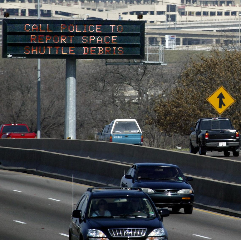 . An electronic highway sign on Interstate 35E just south of downtown Dallas, asks motorists to call the police if they find debris believed to be from the space shuttle Columbia, Sunday, Feb. 2, 2003. The shuttle tore to pieces Saturday 39 miles above Texas as the spaceship re-entered Earth\'s atmosphere, killing all seven astronauts. (AP Photo/Dallas Morning News, Louis Deluca)