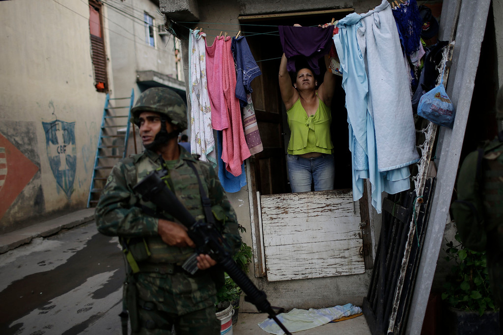 . A woman hangs clothes to dry while a navy soldier enters to occupy the Mare slum complex in Rio de Janeiro, Brazil, Saturday, April 5, 2014. More than 2,000 Brazilian Army soldiers moved into the Mare slum complex early Saturday in a bid to improve security and drive out the heavily armed drug gangs that have ruled the sprawling slum for decades.(AP Photo/Felipe Dana)