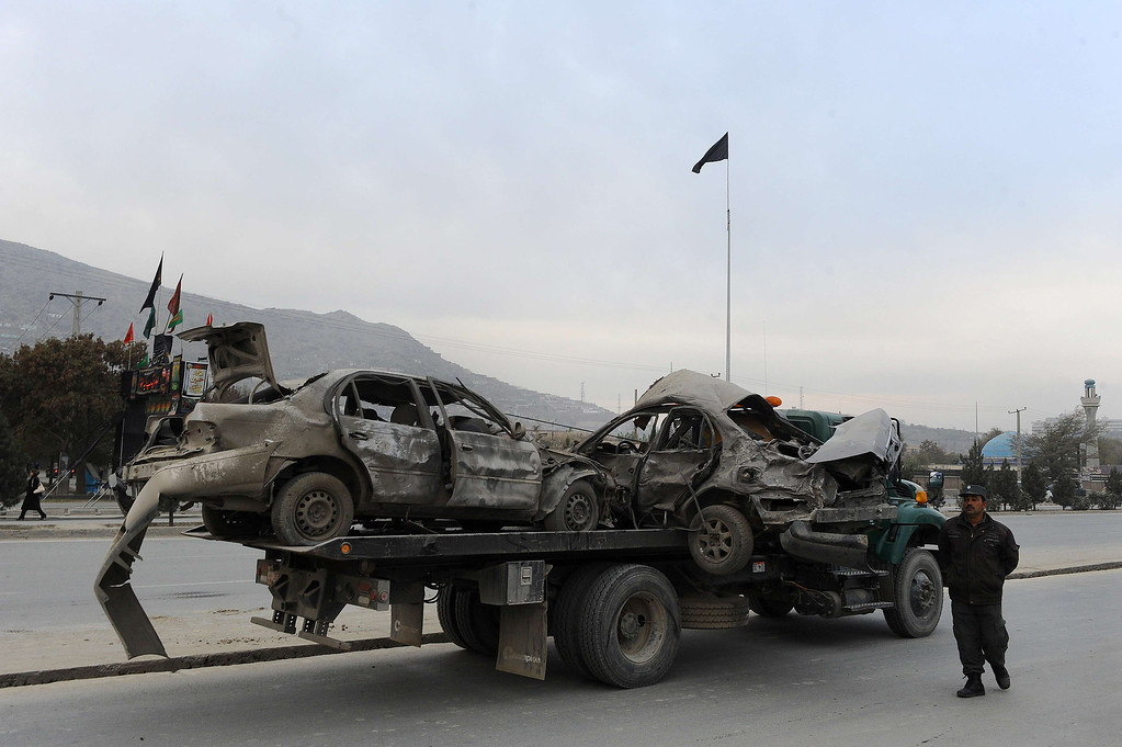 . Afghan police move damaged vehicles from the site of a suicide attack in Kabul on November 16, 2013.    AFP PHOTO / Aref  Karimi/AFP/Getty Images