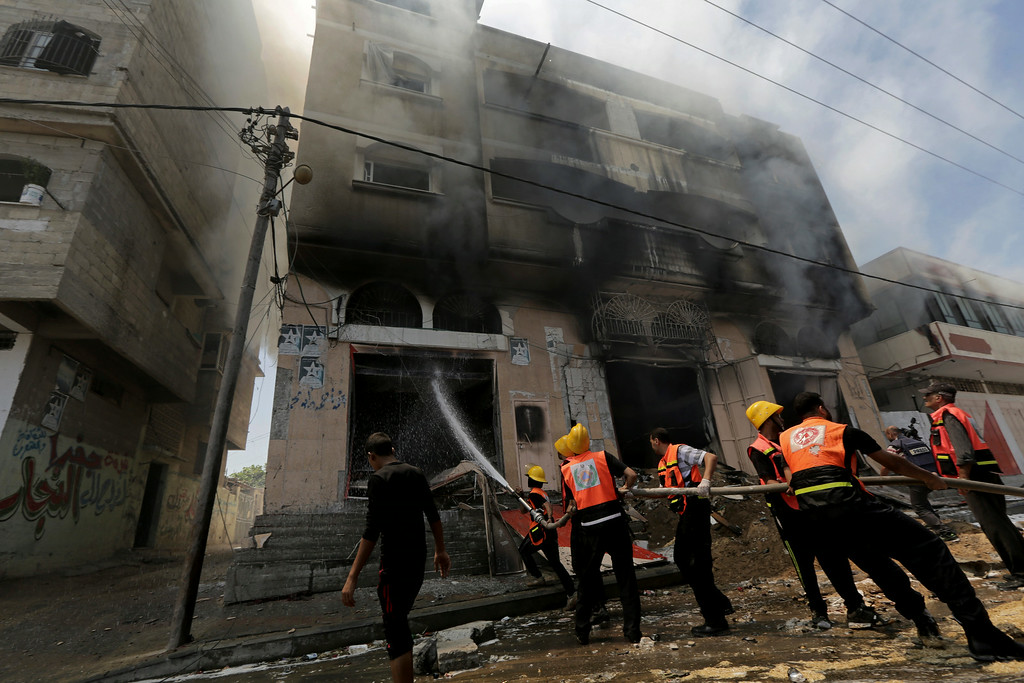 . Palestinian firefighters extinguish a fire in a carpentry shop following an Israeli strike in Gaza, in the northern Gaza Strip, Saturday, Aug. 23, 2014. (AP Photo/Adel Hana)