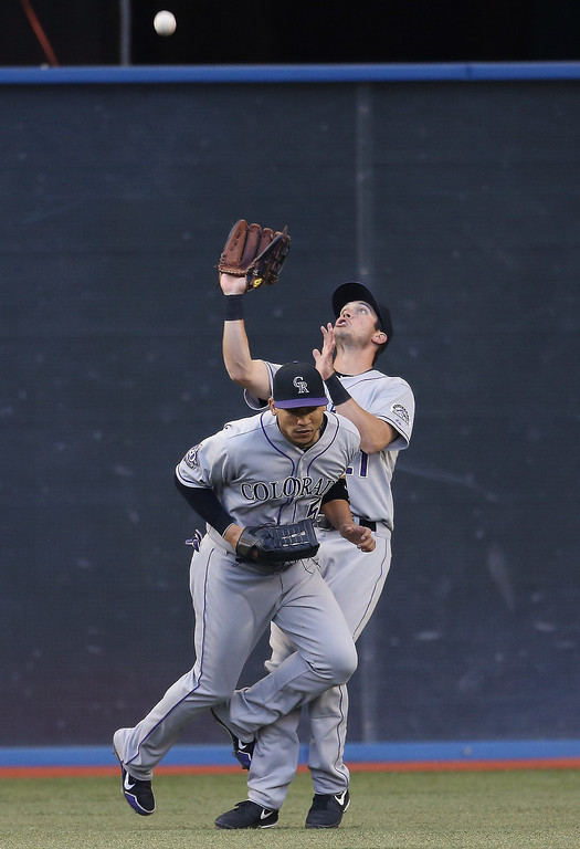 . Tyler Colvin #21 of the Colorado Rockies catches a fly ball in the fourth inning as he nearly collides with Carlos Gonzalez #5 during MLB game action against the Toronto Blue Jays on June 18, 2013 at Rogers Centre in Toronto, Ontario, Canada. (Photo by Tom Szczerbowski/Getty Images)