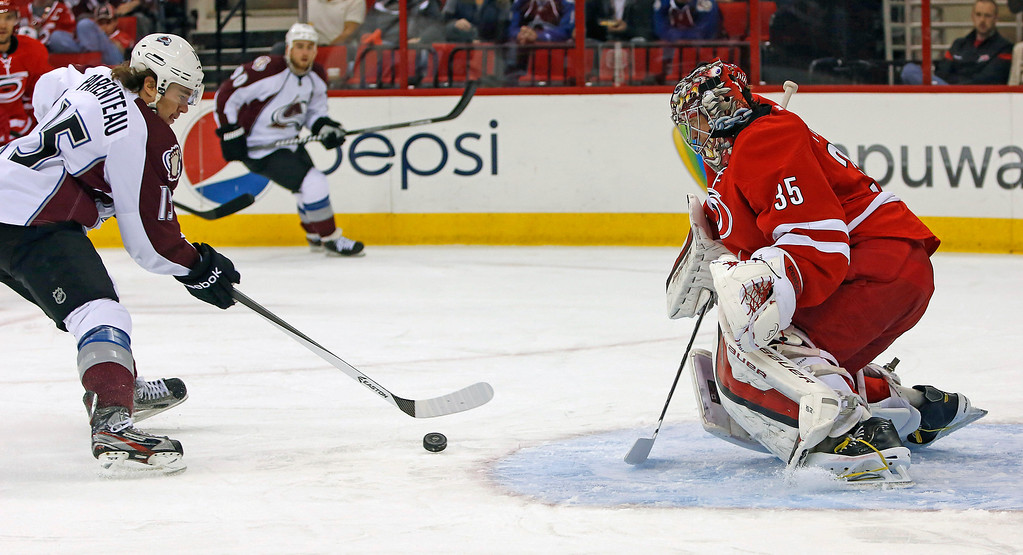 . Colorado Avalanche\'s PA Parenteau (15) breaks away to shoot the puck at Carolina Hurricanes goalie Justin Peters (35) during the first period of an NHL hockey game in Raleigh, N.C., Tuesday, Nov. 12, 2013. (AP Photo/Karl B DeBlaker)