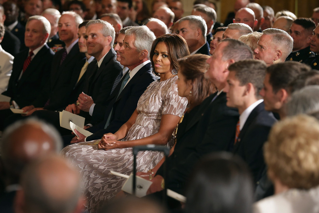 . U.S. first lady Michelle Obama (C) joins Secretary of Defense Chuck Hagel and others for a ceremony where retired Marine Cpl. William \'Kyle\' Carpenter was awarded the Medal of Honor in the East Room of the White House on June 19, 2014 in Washington, DC.   (Photo by Chip Somodevilla/Getty Images)