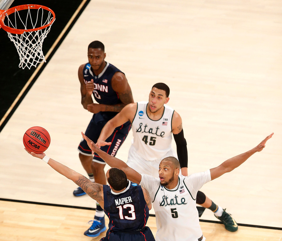 . Connecticut guard Shabazz Napier (13) goes up for a shot against Michigan State forward Adreian Payne (5) during the first half in a regional semifinal at the NCAA college basketball tournament, Sunday, March 30, 2014, in New York. (AP Photo/Julio Cortez)