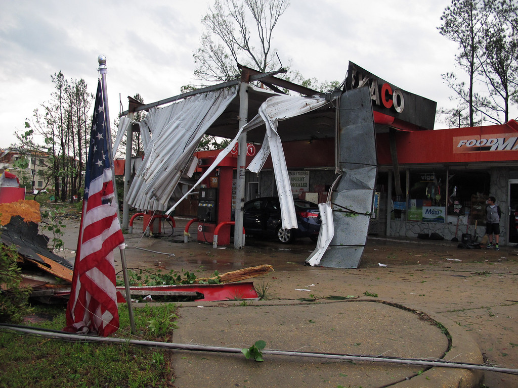 . An American flag stands limp in front of a gas station-convenience store that had its roof mangled by a tornado on Monday, April 28, 2014, in Tupelo, Miss. With parts of the U.S. recovering from deadly tornadoes, more heavy storms are making their way across the South.  (AP Photo/Adrian Sainz).